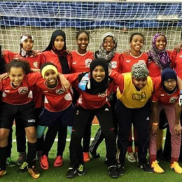A group of East African teenage girls with arms around each others, smiling and standing in front of a soccer goal.