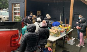 A group of people in masks and coats set food out on a table outside a community center for neighbors in need to pick up