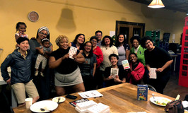 Queer the Land members at a general membership meeting discussing the book Emergent Strategy by adrienne maree brown.