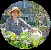 A woman in a sunhat watering a garden