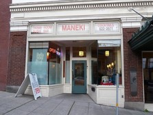 """A storefront of a restaurant with sign atop that says """"Maneki"""""""