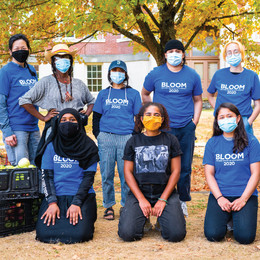 Two adults and six teens face the camera next to baskets of fruit wearing blue shirts that say BLOOM 2020