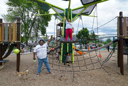 A woman and her daughter stand on playground equipment at a park with their hands raised in a fist.
