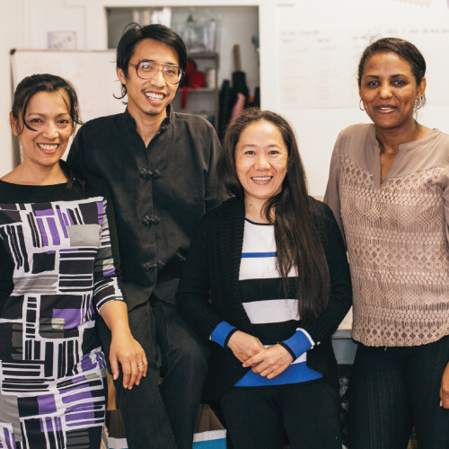photo of four people in a sewing room, smiling