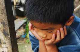 A young Filipino boy looking down with his chin resting in his hands. Photo looking down from above his head slightly.