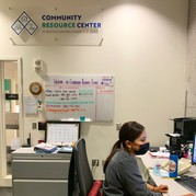 A woman wearing a mask working in the Community Resource Center