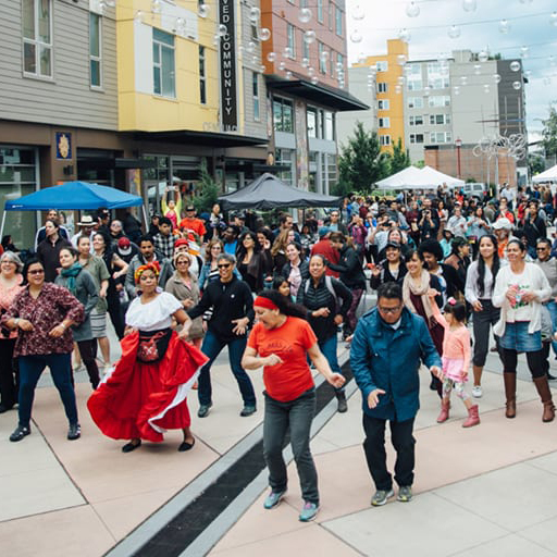 A large group of people performing a choreographed dance in a city square.