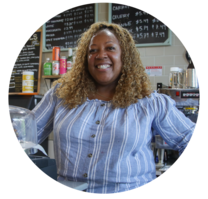 A woman smiling standing at the counter of a cafe and juice bar.
