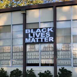 Windows of a building with a Black Lives Matter sign hanging from them.