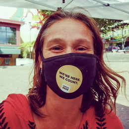 """A woman wearing a face mask that says """"We're Here, We Count"""""""