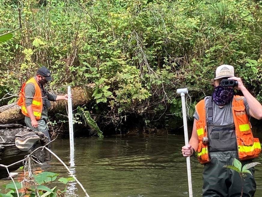 SWM staff use a stadia rod and laser range finder to measure depth and length on the East Fork of Woods Creek.