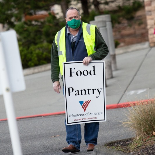 Volunteer from VOA Western Washington directs traffic to drive-through food pantry