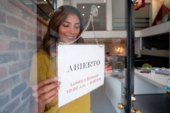 Woman reopening business with sign in Spanish