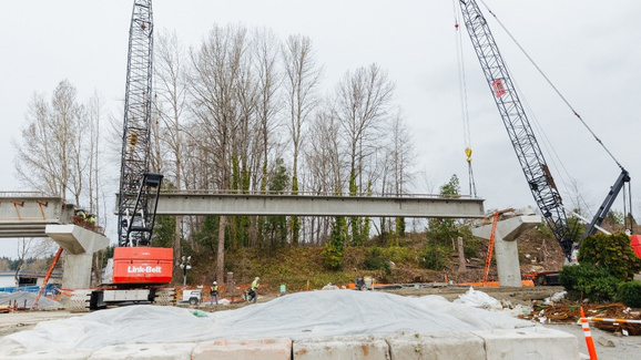 Construction crews will use cranes to place girders between columns