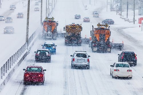 Cars and plow trucks during a snow storm on a highway