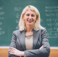 Stock photo of a teacher with a green chalkboard in the background