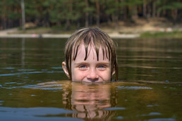 Kid with head peaking out of lake water