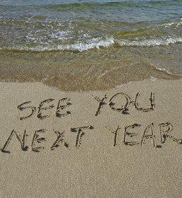 see you next year written in sand on beach