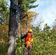 A man climbs to his tree stand wearing a full body harness for safety.