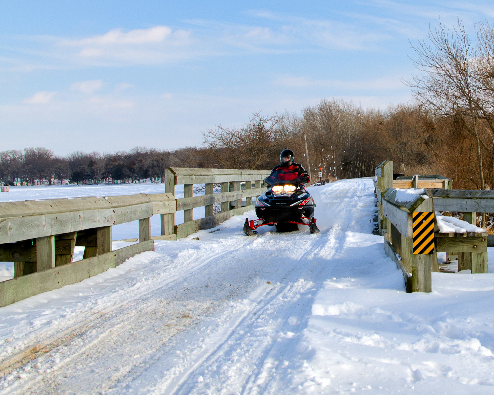 snowmobiler crossing snow-covered bridge