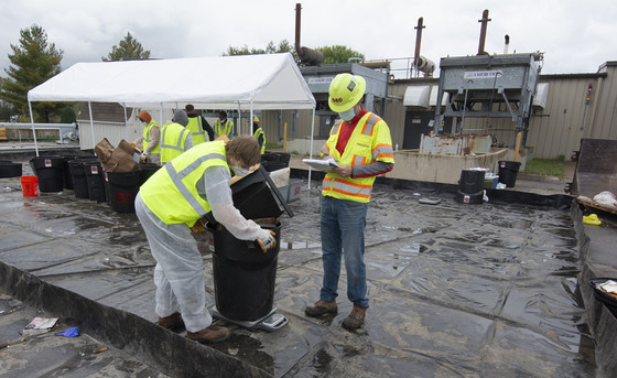 A group of workers weigh trash at a landfill