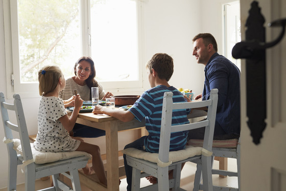 A family of four with young children sits together at the dinner table.