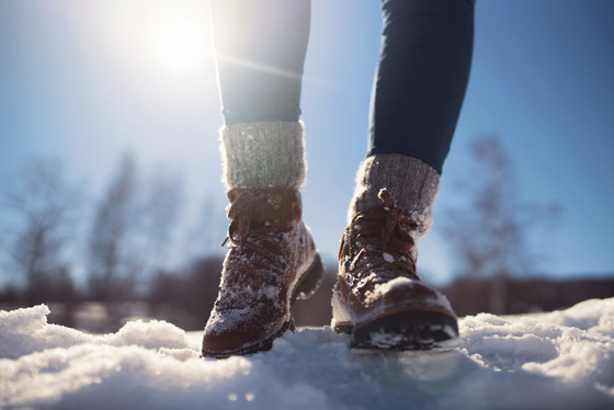 a close-up of a walker's legs wearing winter boots in snow