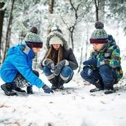 Three children kneel down to observe animal tracks in a wintry forest.