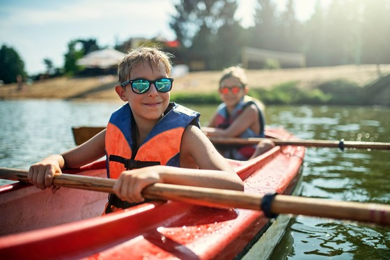two boys wearing lifejackets in a kayak on a lake