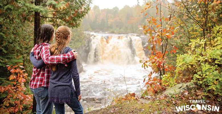 Two girls with their arms around each other looking at Little Manitou falls amid the fall color