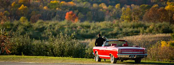 A couple sitting on the hood of their convertible admiring the changing fall foliage