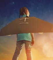 Girl with cardboard wings attached to her back staring at night sky