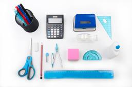 Various school supplies including a calculator, compass and pens