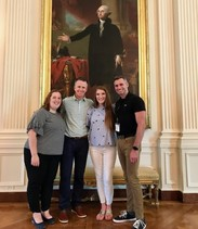 Four teachers posing beneath a large portrait of George Washington