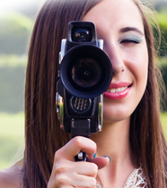 Young woman looking through a video camera