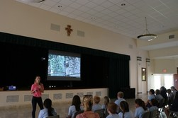 Young female teacher with microphone in front of slide display speaking to middle school students