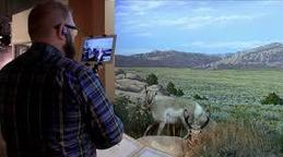 Nathan Doerr of the Wyoming State Museum standing in front of a diorama of an antelope speaking to students virtually