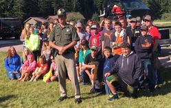 Highway patrolman posing with elementary students on the grass