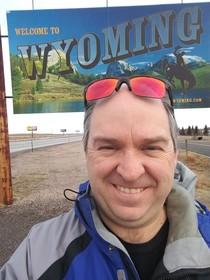 David Stokowski in front of Wyoming sign