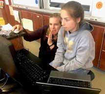 Female teacher and young female student at computer
