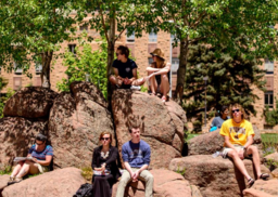 UW students lounging on large boulders on campus