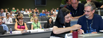 Composite photo of students in theatre-style classroom wearing 3-D glasses and another photo of a female student visiting with a male instructor