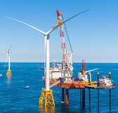 Photo of wind turbine being installed in the ocean by a large crane on a platform
