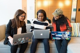 Three women with laptops smiling