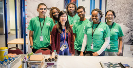Students at the Science Museum of Minnesota all wearing green shirts and posing and smiling