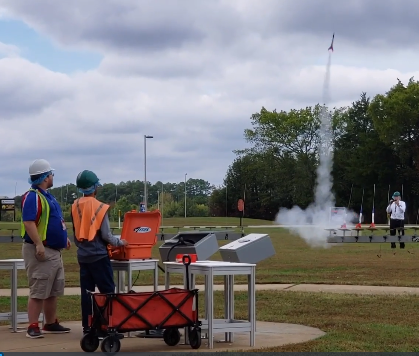 Student launching a small rocket with adult supervision