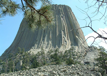 Devils Tower with boulder field and evergreen trees in the foreground