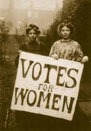 "Two women from the 19th century holding a sign that reads, ""Votes for Women"""