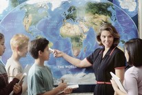 Teacher in front of students pointing to world map