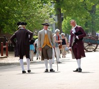 Three men in period costumes standing in Colonial Williamsburg